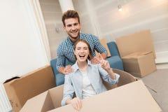 获得年轻的夫妇乐趣,当移动向新的公寓时 移动的新婚佳偶 女孩在箱子坐 库存图片