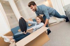 获得年轻的夫妇乐趣,当移动向新的公寓时 移动的新婚佳偶 女孩在箱子坐 免版税库存照片