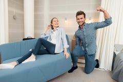 获得年轻的夫妇乐趣,当移动向新的公寓时 移动的新婚佳偶 女孩坐长沙发 免版税库存图片