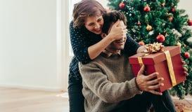获得年轻的夫妇庆祝与礼物的乐趣圣诞节 图库摄影