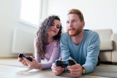 获得年轻的夫妇打电子游戏的乐趣 免版税库存图片