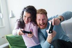 获得年轻的夫妇打电子游戏的乐趣 库存图片
