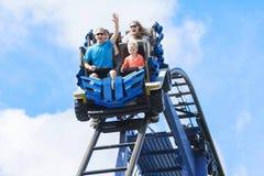 获得年轻的家庭乘坐过山车的乐趣在主题乐园 库存图片