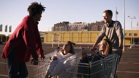 获得年轻的朋友在购物车的乐趣 使用与购物车的不同种族的青年人 站立的男孩近 影视素材