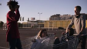 获得年轻的朋友在购物车的乐趣 使用与购物车的不同种族的青年人 Malefriends身分 影视素材