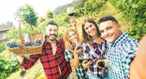 获得年轻的朋友采取selfie的乐趣在室外酿酒厂的葡萄园-在一起享受收获的愉快的人民的友谊概念 免版税库存照片