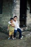 获得年轻的男孩乐趣在他们的家外面 免版税图库摄影