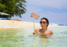 获得年轻美丽和愉快的亚裔中国的妇女在拍与手机照相机的海水的乐趣selfie照片在天堂b 库存照片