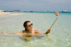 获得年轻美丽和愉快的亚裔中国的妇女在拍与手机照相机的海水的乐趣selfie照片在天堂b 图库摄影