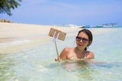 获得年轻美丽和愉快的亚裔中国的妇女在拍与手机照相机的海水的乐趣selfie照片在天堂b 免版税图库摄影