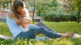 获得年轻运动的母亲和小逗人喜爱的女儿愉快的家庭乐趣户外 库存照片