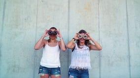 获得很多乐趣一起和使用与油炸圈饼的两个美丽的女朋友 股票录像