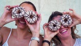 获得很多乐趣一起和使用与油炸圈饼的两个美丽的女朋友 影视素材