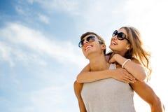 获得微笑的夫妇在天空背景的乐趣 免版税库存照片