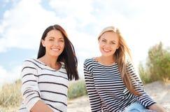 获得微笑的女朋友在海滩的乐趣 免版税库存图片