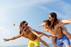 获得微笑的朋友在夏天海滩的乐趣 库存照片