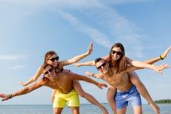 获得微笑的朋友在夏天海滩的乐趣 图库摄影