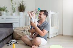获得微笑的父亲画象与他的婴孩地板的乐趣在flo 免版税库存图片