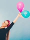 获得微笑的疯狂的女孩与气球的乐趣 免版税库存照片