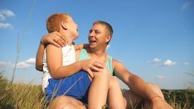获得微笑的红发的男孩一起在绿草坐有他的父亲的草坪和室外的乐趣 愉快的爸爸 股票视频