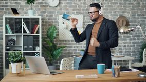 获得快乐的企业家听音乐跳舞佩带的耳机的乐趣 股票录像