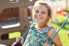 获得快乐的女孩在操场的乐趣 库存照片