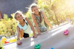 获得快乐的孩子在操场的乐趣 免版税库存图片