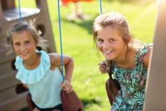 获得快乐的孩子在操场的乐趣 库存照片