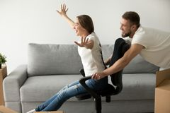 获得快乐的无忧无虑的夫妇使用与椅子的乐趣移动  免版税库存照片