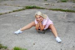获得性感的女孩在滑板的乐趣 免版税库存图片