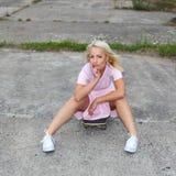 获得性感的女孩在滑板的乐趣 免版税图库摄影