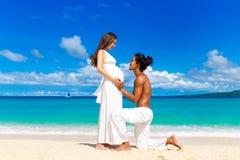 获得愉快和年轻人怀孕的夫妇在一个热带海滩的乐趣 免版税库存图片