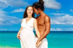 获得愉快和年轻人怀孕的夫妇在一个热带海滩的乐趣 库存图片
