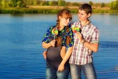 获得愉快和年轻人怀孕的夫妇在海滩的乐趣 夏天 免版税库存图片