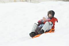 获得愉快的兄弟姐妹在冬天橙色塑料雪滑子的下坡乐趣 免版税库存图片