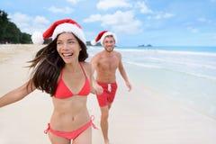 获得愉快的圣诞节的夫妇跑在海滩的乐趣 免版税库存照片