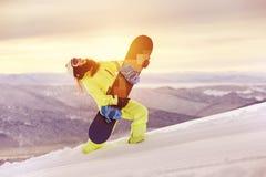 获得愉快的夫人的挡雪板与雪板的乐趣 免版税库存图片