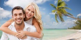 获得愉快的夫妇在海滩背景的乐趣 免版税库存照片