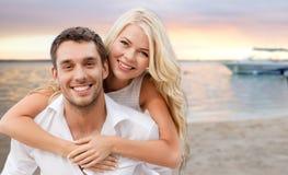 获得愉快的夫妇在海滩背景的乐趣 免版税库存图片