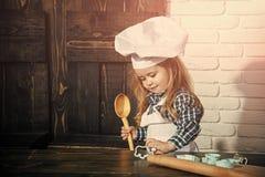 获得愉快的孩子乐趣 厨师帽子的男孩厨师和围裙在厨房里 免版税库存照片