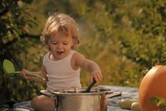 获得愉快的孩子乐趣 有菜的滑稽的男婴 免版税库存照片