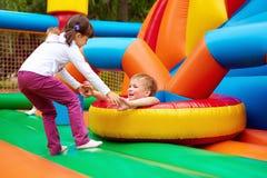 获得愉快的孩子在可膨胀的吸引力操场的乐趣 免版税库存图片