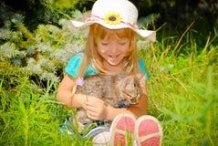 获得愉快的孩子的女孩乐趣有小猫的夏天公园 免版税图库摄影