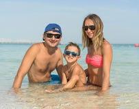 获得愉快的家庭在热带白色海滩的乐趣 母亲,父亲, 免版税库存图片