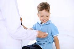 获得愉快的小男孩乐趣,当是时由医生审查由听诊器 医疗保健、保险和帮助概念 免版税库存图片