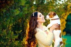 获得愉快的少妇拥抱和与她的杰克罗素狗的乐趣户外 库存图片