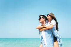 获得愉快的年轻夫妇穿戴的太阳镜在天空蔚蓝和海滩的乐趣 图库摄影