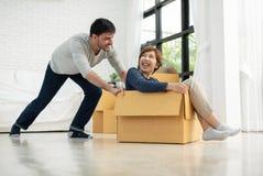 获得愉快的年轻的夫妇与纸板箱的乐趣 图库摄影