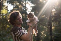 获得愉快的快乐的父亲乐趣投掷悬而未决他的孩子反对日落背景-故意太阳强光和 免版税库存照片