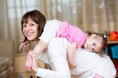 获得愉快的母亲拿着她的女儿后面的乐趣 库存照片